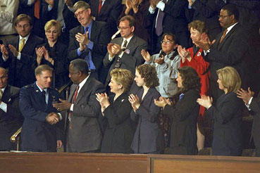 Photo: First Lady Hillary Rodham Clinton and guests applaud Captain John Cherrey.