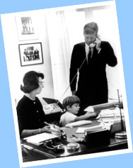 Evelyn Lincoln, President Kennedy's Personal Secretary, looks on while the President takes an important phone call and his son, John F. Kennedy, Jr., plays with her typewriter.