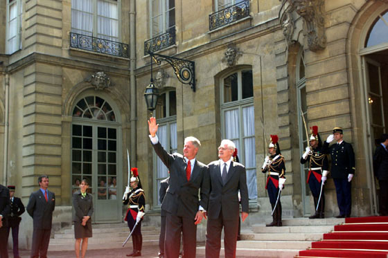President Clinton, accompanied by French Prime Minister Lionel Jospin, waves to the crowd outside the Prime Minister's residence, Hôtel Matignon.
