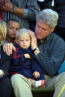 President Clinton comforts a young boy at Stenkovic I refugee camp in Macedonia.