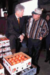 The President stops to speak to a local farmer at the Hermitage Tomato Co-operative in Arkansas; Photo by Ralph Alswnag, November 5, 1999.
