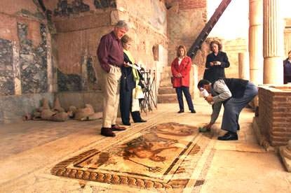 A man wets down the stones of a tile fresco to show off its details, which have dulled from age.