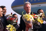President Clinton is presented with numerous floral  bouquets upon his arrival at Mumbai Airport.
