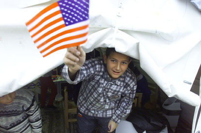 A boy waves the American flag as he waits for a visit by President Clinton.