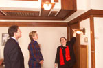 Karen Sweeney, Restoration Architect for the Robie House, displays some of Wright's innovative designs as the First Lady and Thomas Pritzker look on.